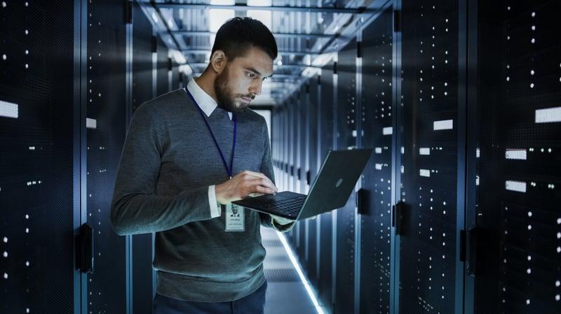 man-holding-open-laptop-in-data-center-server-room-with-dim-lighting